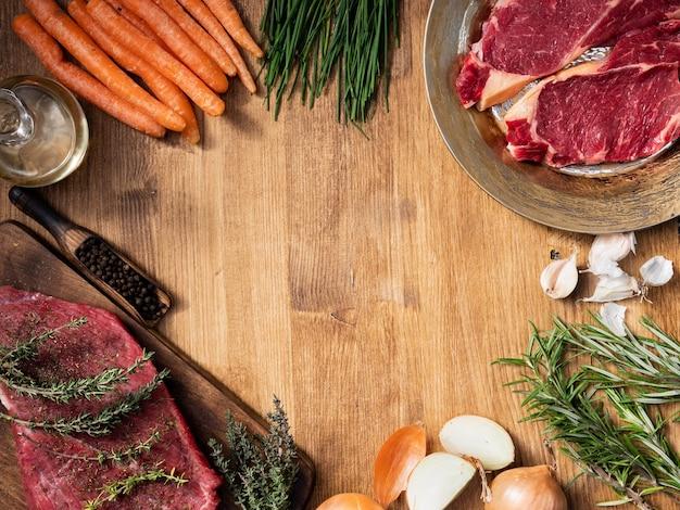 Vista superior de um pedaço de carne vermelha na placa de madeira da cozinha e dois pedaços de lombo em um prato vintage. copie o espaço disponível.