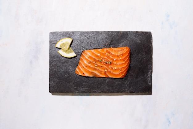 Vista superior de um pedaço de salmão cru em uma placa de ardósia e fatias de limão