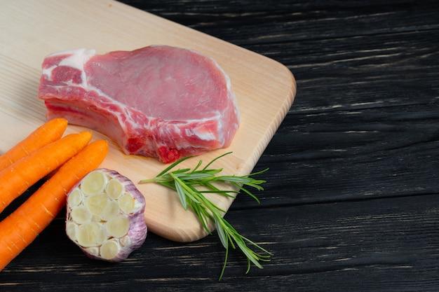 Vista superior de um pedaços de bifes de costeleta de porco cru com tomate cereja alecrim e alho em uma placa de corte.