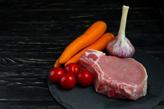 Vista superior de um pedaços de bifes de costeleta de porco cru com tomate cereja cenoura e alho em uma tábua de pedra preta.
