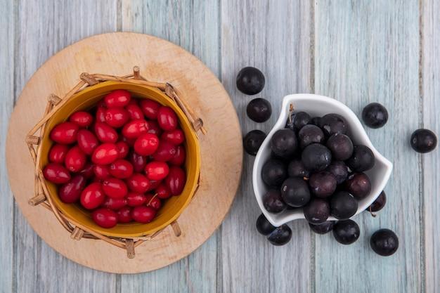 Vista superior de um pequeno abrunheiro roxo escuro em uma tigela branca com bagas vermelhas de cornel em um balde em uma placa de cozinha de madeira em um fundo cinza de madeira