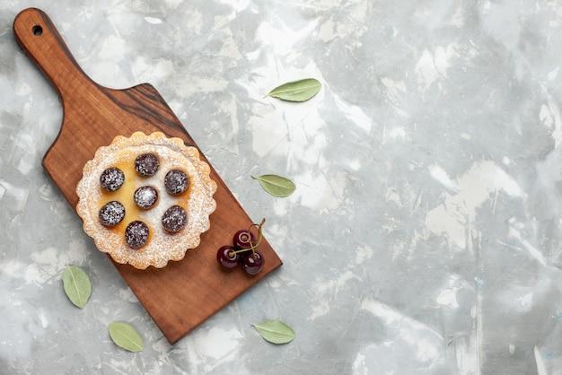 Vista superior de um pequeno bolo com açúcar em pó e frutas na luz, bolo assar torta doce