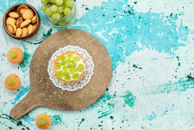 Vista superior de um pequeno bolo com creme delicioso e biscoitos de uvas frescas e fatiados isolados na mesa de luz azul, bolo de frutas doces
