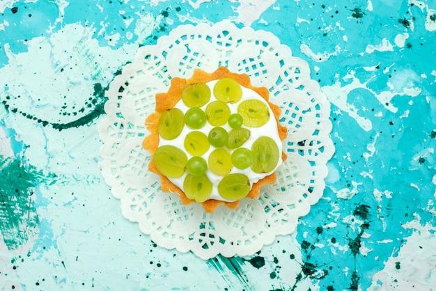 Vista superior de um pequeno bolo com creme delicioso e uvas verdes fatiadas isoladas em azul, bolo doce de frutas