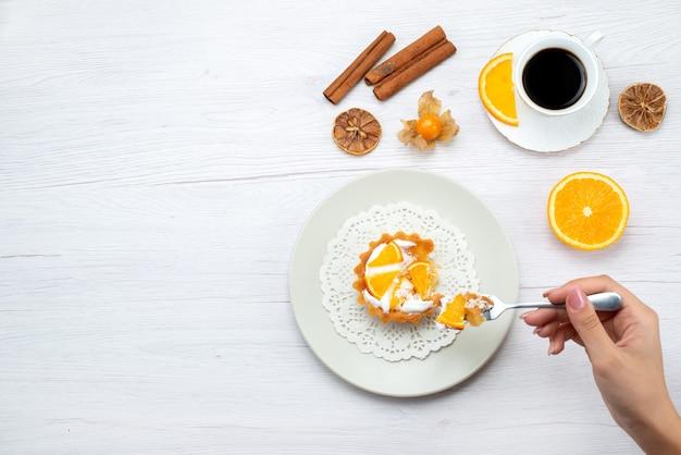 Vista superior de um pequeno bolo com creme e fatias de laranjas sendo comido por uma mulher junto com café e canela na mesa leve, bolo de frutas doce açúcar