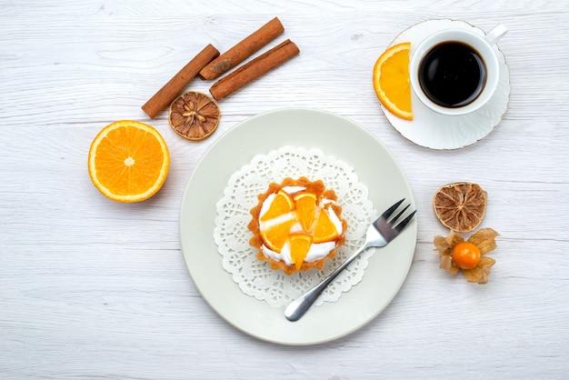 Vista superior de um pequeno bolo com creme e laranjas fatiadas junto com café e canela na mesa leve, bolo de frutas doce de biscoito