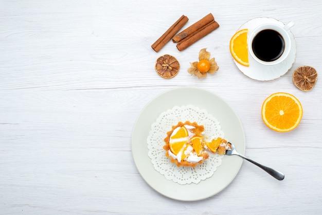 Vista superior de um pequeno bolo com creme e laranjas fatiadas junto com uma xícara de café e canela na mesa leve, biscoito de bolo de frutas doce