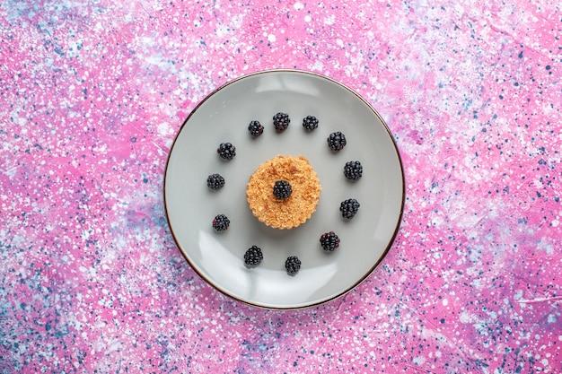 Vista superior de um pequeno bolo com frutas dentro do prato na superfície rosa