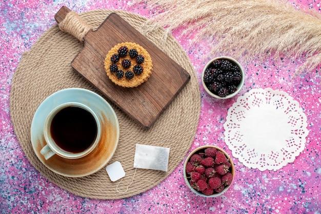 Vista superior de um pequeno bolo com frutas diferentes e uma xícara de chá na superfície rosa
