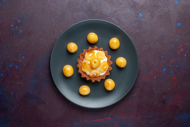 Vista superior de um pequeno bolo cremoso com cerejas frescas dentro do prato na superfície escura