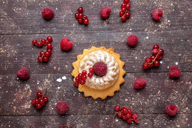 Vista superior de um pequeno bolo delicioso com açúcar em pó junto com framboesas e cranberries ao longo da mesa marrom, biscoito de bolo de frutas vermelhas