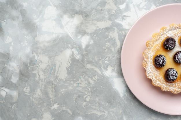 Vista superior de um pequeno bolo delicioso com cerejas dentro do prato na luz