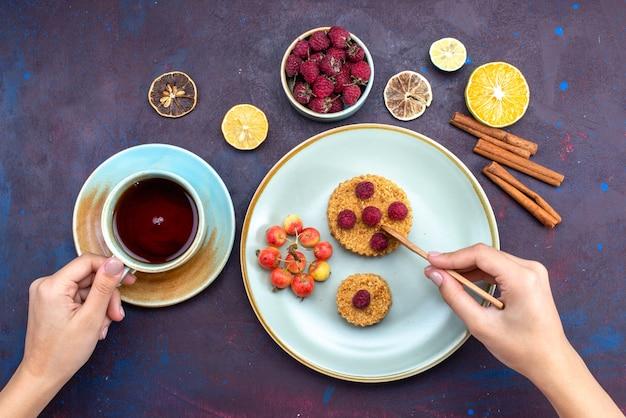 Vista superior de um pequeno bolo redondo com framboesas frescas dentro do prato com chá de frutas e canela na superfície escura