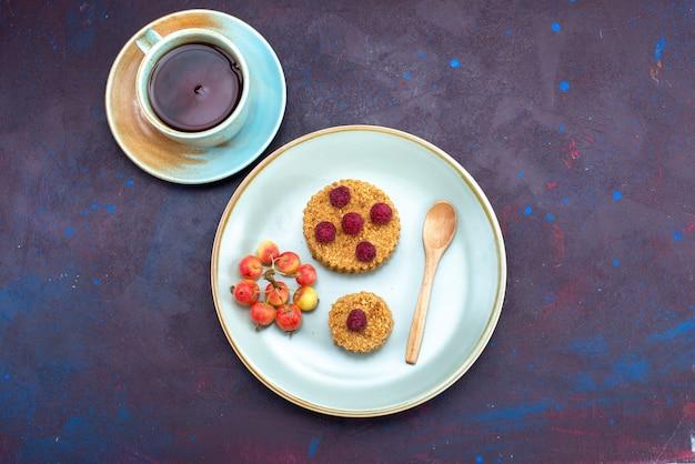 Vista superior de um pequeno bolo redondo com framboesas frescas dentro do prato com chá na superfície escura