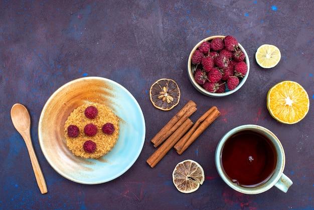 Vista superior de um pequeno bolo redondo com framboesas frescas dentro do prato com frutas e canela na superfície escura