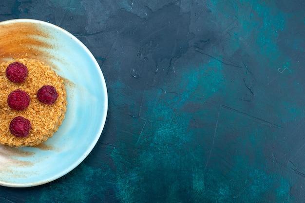Vista superior de um pequeno bolo redondo com framboesas frescas dentro do prato na superfície azul escura