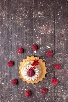Vista superior de um pequeno bolo simples com açúcar em pó, framboesa e cranberries em madeira marrom, bolo de frutas de baga