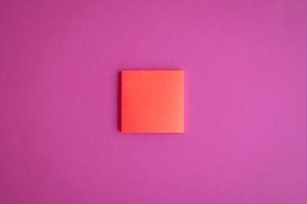 Vista superior de um post-it de papel em branco laranja em um fundo rosa com um espaço de cópia