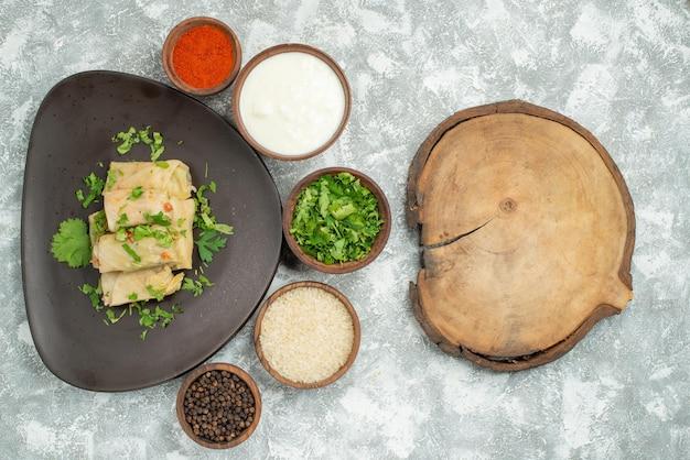 Vista superior de um prato à distância em um prato de repolho recheado com ervas no prato ao lado de creme de leite de especiarias e uma tábua de madeira na mesa cinza