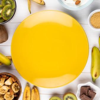 Vista superior de um prato amarelo e frutas frescas de banana e kiwi, dispostas em branco