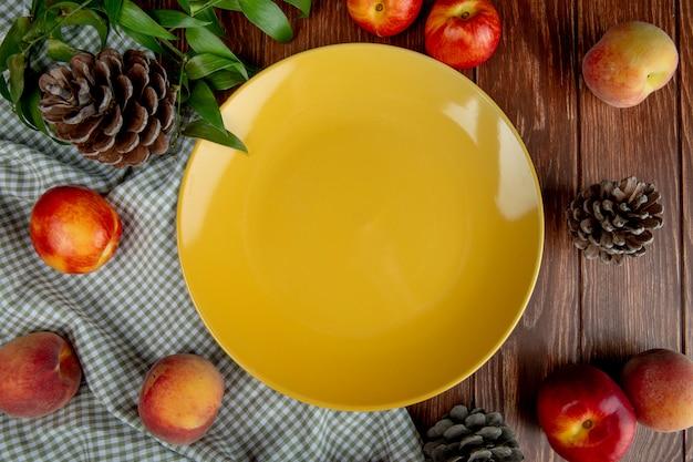 Vista superior de um prato amarelo vazio e pêssegos doces frescos com nectarinas e cones em tecido xadrez na mesa rústica de madeira