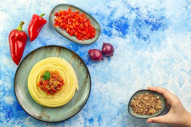 Vista superior de um prato cinza com deliciosas cebolas spagetti picadas e pimenta vermelha inteira e uma mão segurando a carne na mesa azul