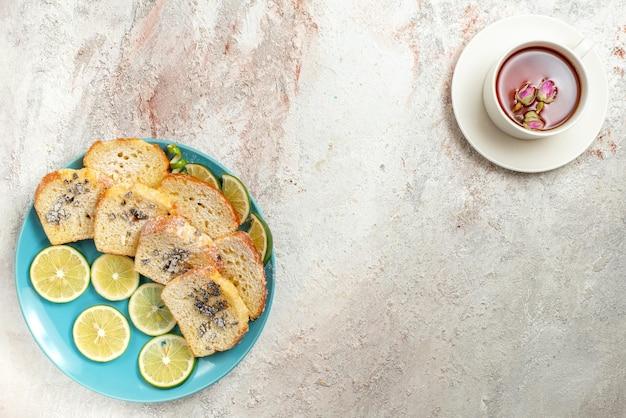 Vista superior de um prato com uma xícara de chá azul no prato de bolo e limão fatiado e uma xícara de chá preto na mesa