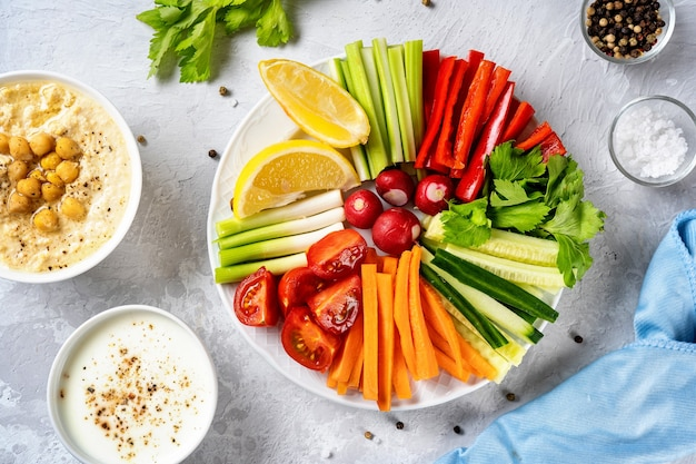 Vista superior de um prato com vegetais coloridos fatiados e molhos