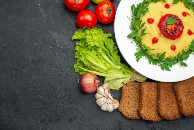 Vista superior de um prato de batata com pasta de pão preto e vegetais no escuro