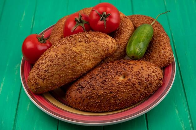 Vista superior de um prato de pães com legumes frescos, como pepino e tomate, em um fundo verde de madeira
