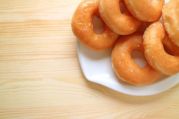 Vista superior de um prato de rosquinhas com cobertura de açúcar em uma mesa de madeira com espaço para cópia