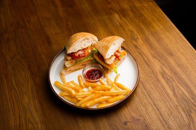 Vista superior de um prato de sanduíche e batatas fritas em uma mesa de madeira.