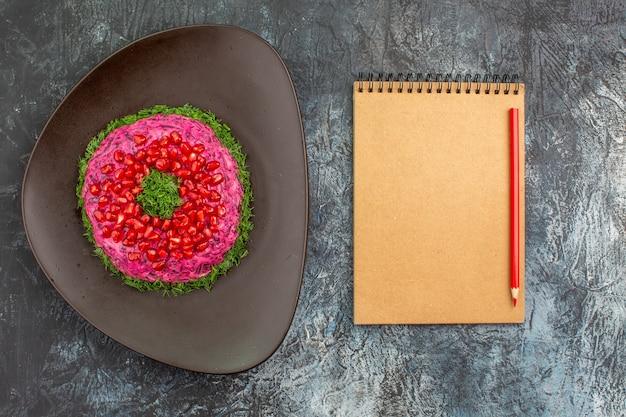 Vista superior de um prato distante com ervas, sementes de romã, caderno e lápis