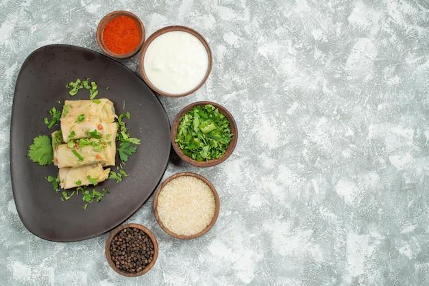 Vista superior de um prato distante no prato repolho recheado com ervas no prato ao lado de especiarias e creme de leite na mesa cinza