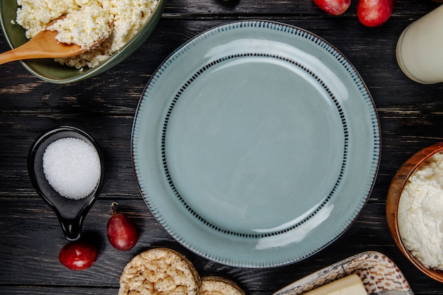 Vista superior de um prato, queijo cottage em uma tigela, uvas doces frescas e açúcar em um pires na mesa de madeira escura