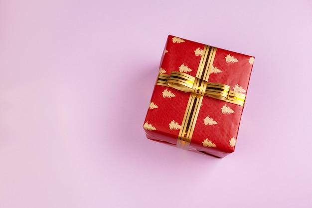 Vista superior de um presente decorado com um laço no fundo rosa