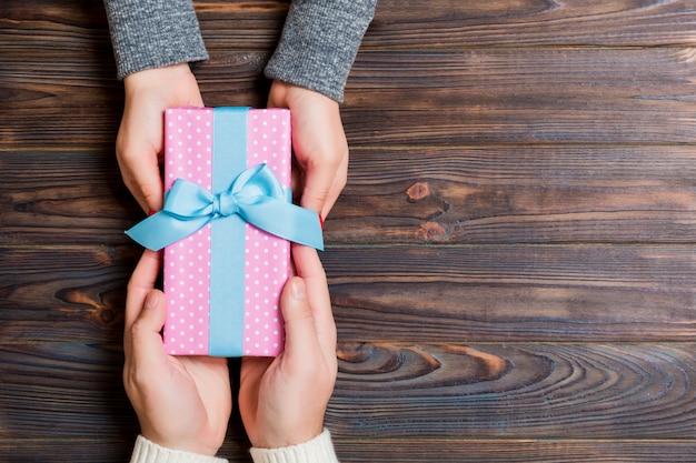Vista superior de um presente nas mãos masculinas e femininas em madeira.