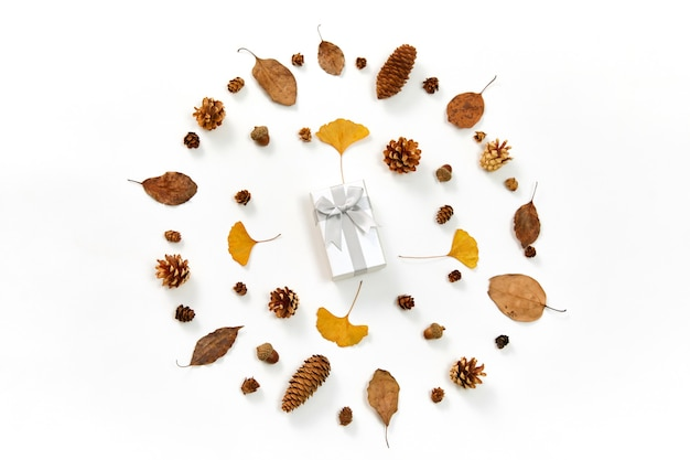 Vista superior de um presente no meio de uma coroa de flores feita de folhas de outono e cones de coníferas em branco