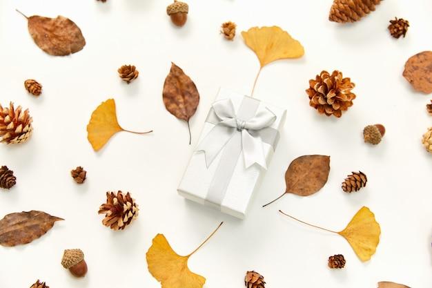 Vista superior de um presente no meio de uma coroa de flores feita de folhas de outono e cones de coníferas