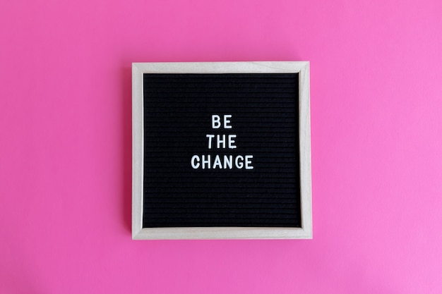 Vista superior de um quadro negro com moldura branca e uma hashtag em um fundo rosa. a mudança