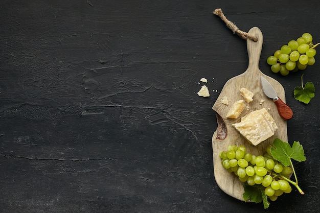 Vista superior de um saboroso prato de queijo com frutas e uvas em um prato de madeira de cozinha no fundo de pedra preta