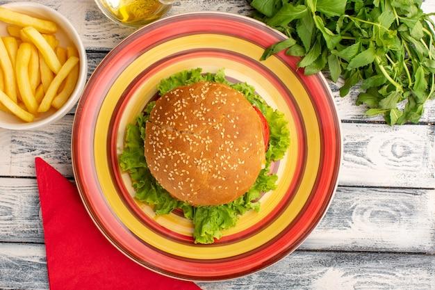 Vista superior de um saboroso sanduíche de frango com salada verde e batatas fritas de legumes em uma superfície cinza rústica