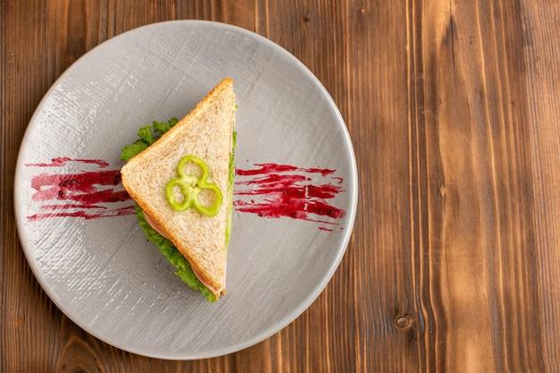 Vista superior de um sanduíche saboroso dentro do prato na mesa de madeira