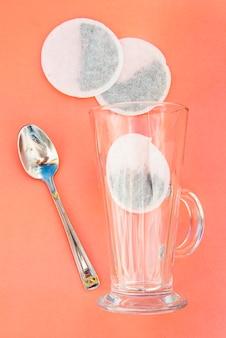 Vista superior de um saquinho de chá e copo de vidro vazio, isolado no rosa.