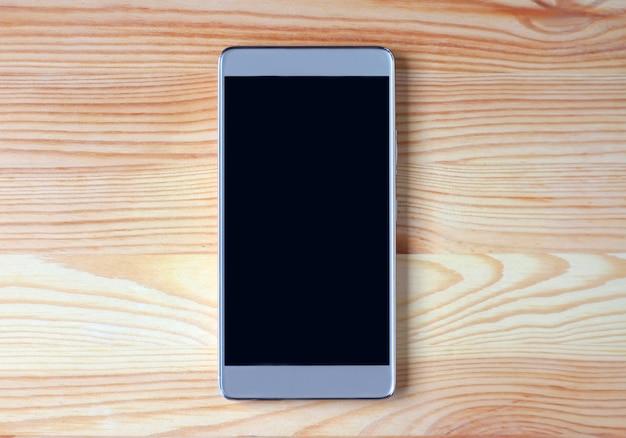 Vista superior de um smartphone de tela preta vazia isolado na mesa de madeira marrom clara