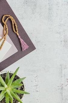Vista superior de um tapete de ioga violeta, contas de madeira ruins na superfície branca. acessórios essenciais para a prática de yoga e meditação. copie o espaço
