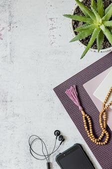 Vista superior de um tapete de ioga violeta, contas de madeira ruins sobre fundo branco. acessórios essenciais para a prática de yoga e meditação. copie o espaço