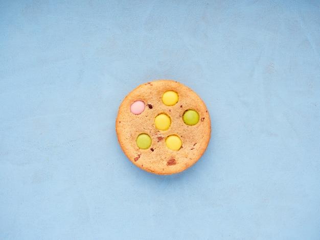 Vista superior de um único cookie com doces coloridos incorporados no topo de uma superfície azul