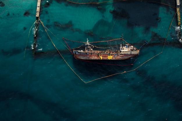 Vista superior de um velho petroleiro que encalhou e capotou