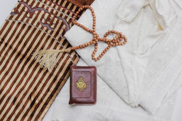 Vista superior de um vestido muçulmano chamado mukena e contas de oração com o livro sagrado de al quran e tapete de oração